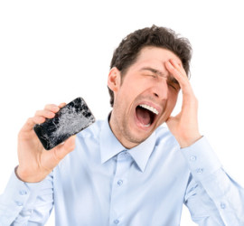 Handsome angry businessman showing broken smartphone with crashed screen. Isolated on white background.